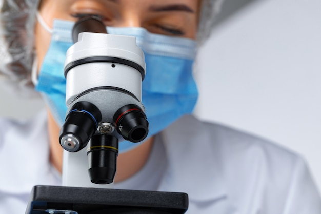 Close up photo of woman scientist working with microscope