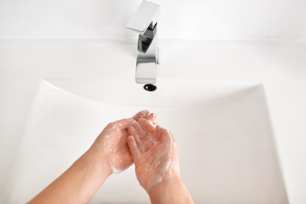 Close up photo of woman washing hands in white clean basin in home washroom, top view.