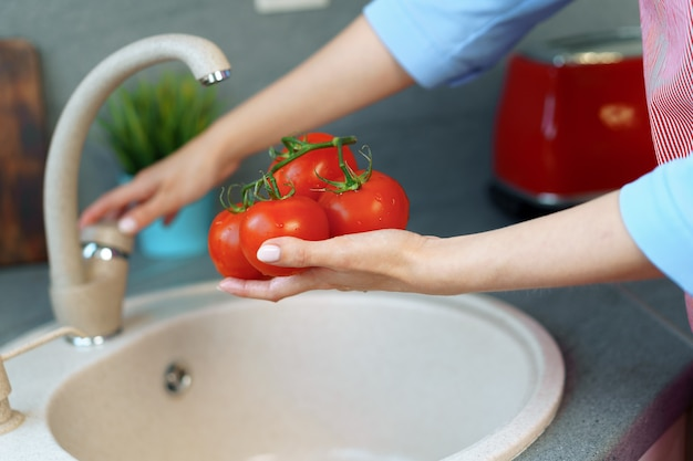 Close up photo of woman washing tomatoes in a sink