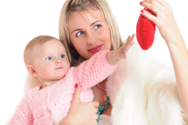 Close-up photo of a woman with child looking with interest at toy in form of red heart