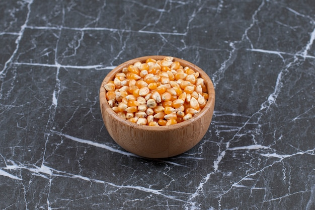 Close up photo of wooden bowl full with corn seeds.