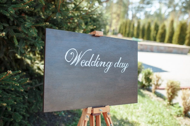 The close-up photo of the wooden plaque with the signs welcome to the wedding standing in the street