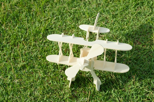 Close up photo of wooden toy airplane against  on grass