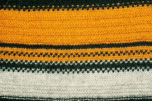 Close up photo of yellow, green and white striped knitted sweater texture as abstract background.