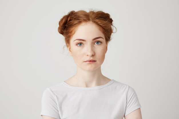 Close up photo of young beautiful ginger girl with buns .