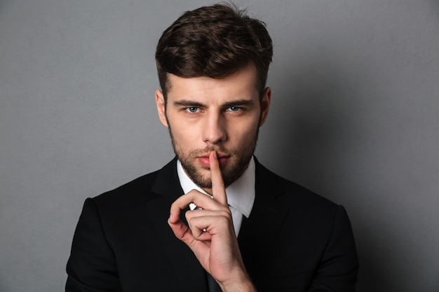Close-up photo of young handsome man in black suit showing silence gesture,