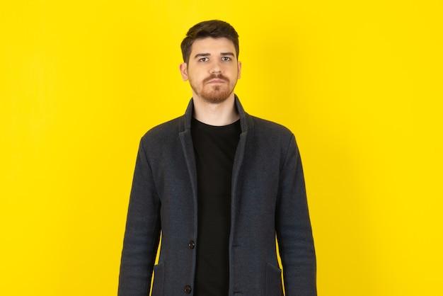 Chiuda sulla foto di giovane uomo bello su un giallo.