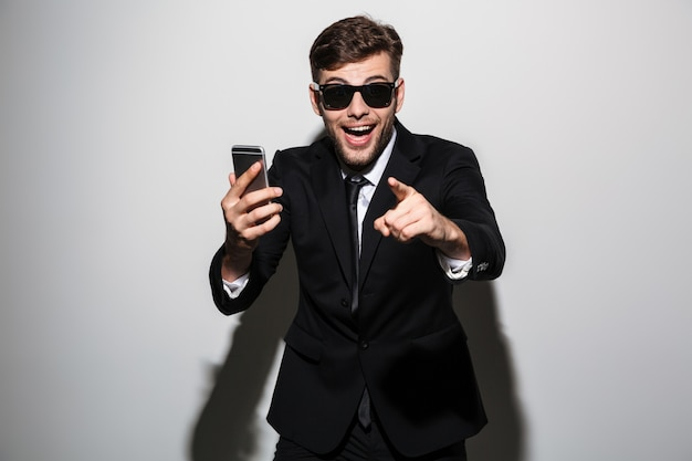 Close-up photo of young happy exited attractive man in sunglasses holding smartphone and pointing with finger on you