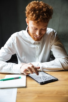 Close-up photo of young happy readhead bearded man using digital tablet at workplace
