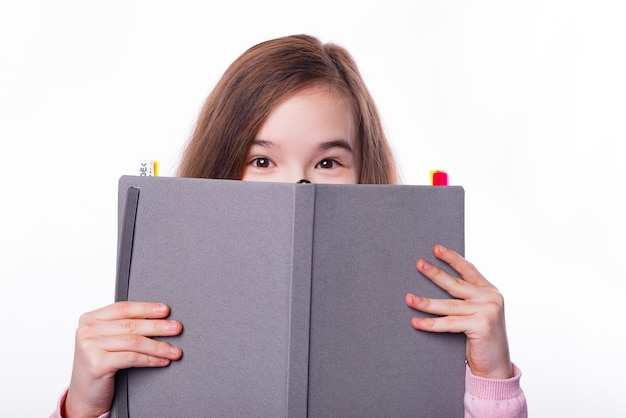 Close up photo of young school girl covering face with planner