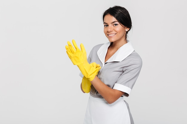 Close-up photo of young smiling brunette maid in uniform putting on yellow rubber gloves while standing