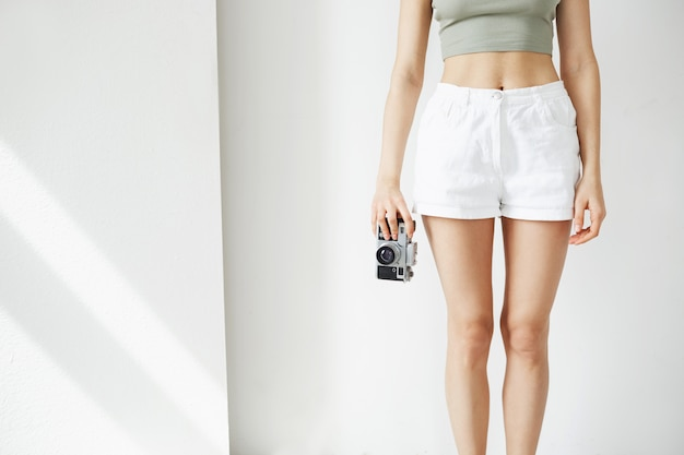 Close up photo of young teenage woman holding old camera over white wall.
