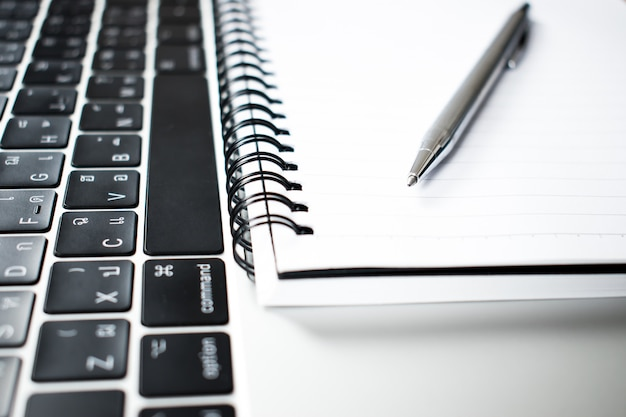 A close up photograph of a pen placed in a notebook and a computer of a young businessman.