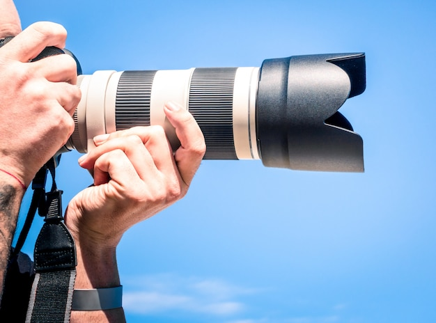 Close up of photographer taking photo with zoom lens