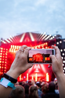 Close up of photographing with smartphone during a concert.