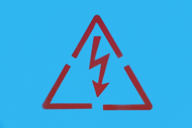 Close up photography of a red painted electricity warning sign on a blue metal background