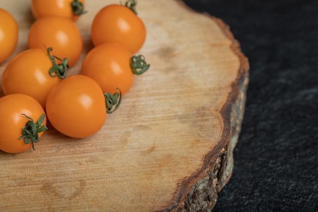 나무 보드에 원시 체리 토마토의 사진을 닫습니다. 고품질 사진