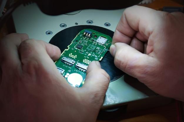 Фотографии крупным планом, показывающие процесс ремонта мобильного телефона. ремонт телефонов под микроскопом. мобильная плата. ремонт гаджетов в домашних условиях крупным планом. мужские руки проверяют работоспособность телефона