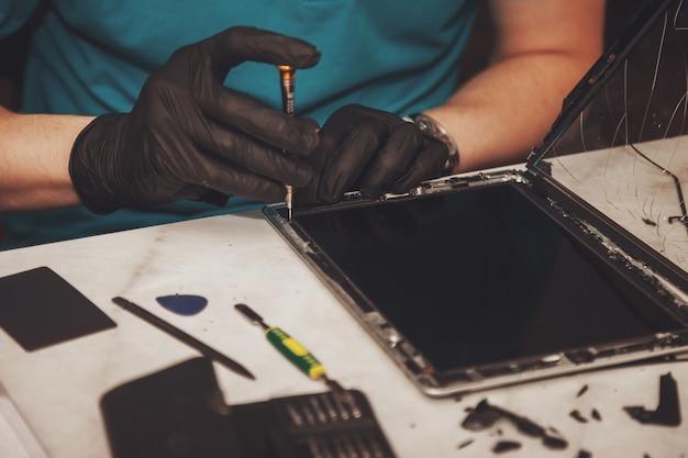 タブレットデバイスの修理のプロセスを示す写真を閉じます。プロのコンピューターとタブレットの修理店またはサービス。エレクトロニクスとガジェットのコンセプト。コピースペース Premium写真