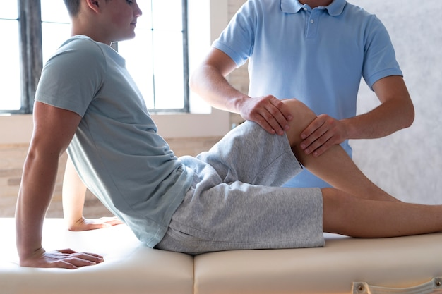 Close upphysiotherapist massaging patient