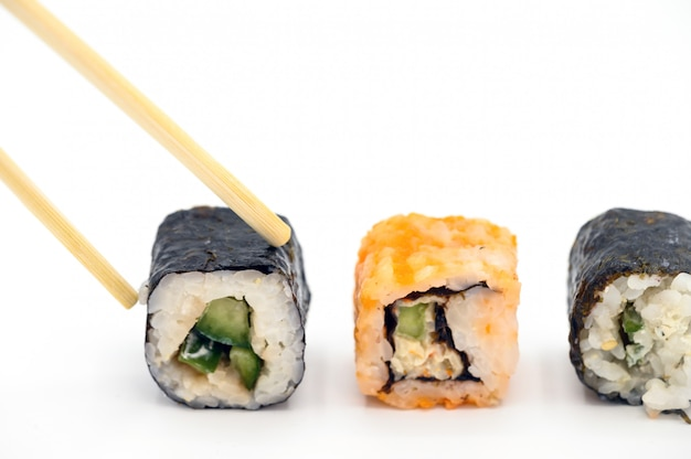 Close up of picking with chopsticks fresh prepared sushi on white isolated background.