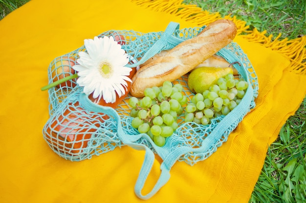 Close up of picnic bag with food, fruits and flower on the yellow cover on the green grass