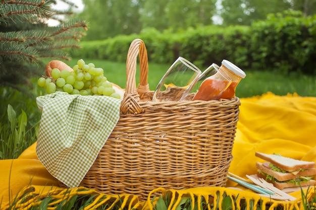 Close up of picnic basket with food, fruits and flower on the yellow cover on the green grass