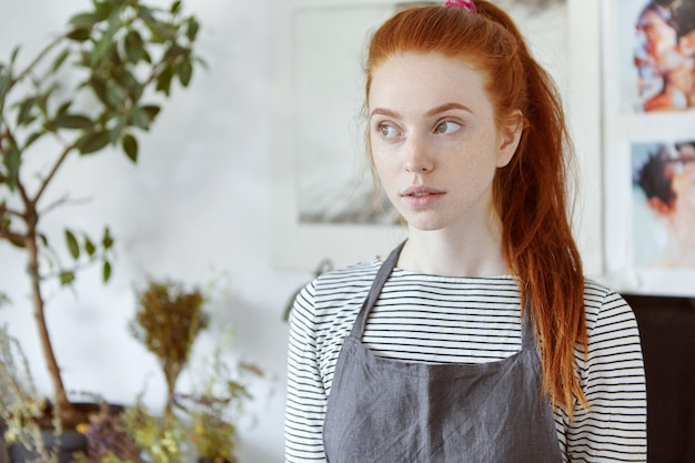 Close up picture of beautiful freckled red haired european girl student of arts school in college workshop