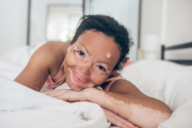 A close up picture of a cute mulatta in bed