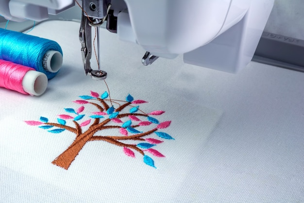 Close up picture of embroidery machine and two threads cyan and pink color.