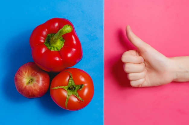 Close up picture of fresh red apple and woman showing thumbs up