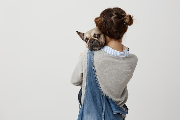 Close up picture of girl with hair in double buns standing backsides holding her puppy in hands. female teenager wearing denim jumpsuit expressing love to her french bulldog. feelings, attitude