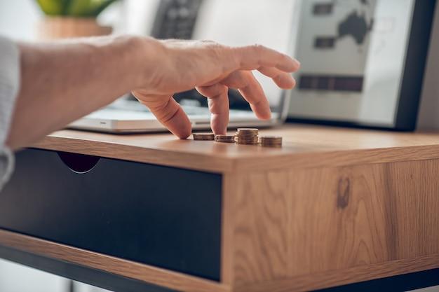 テーブルの上のコインを計算している男の写真をクローズアップ