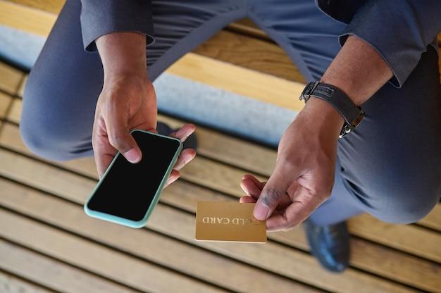 신용 카드와 스마트폰을 들고 있는 남자의 클로즈업 사진