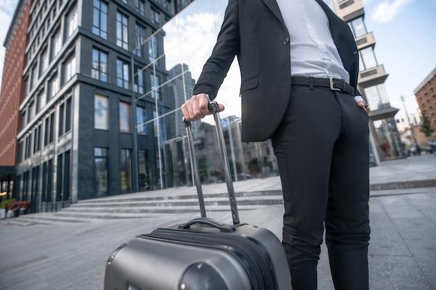 黒いスーツとスーツケースを着た男の写真をクローズアップ