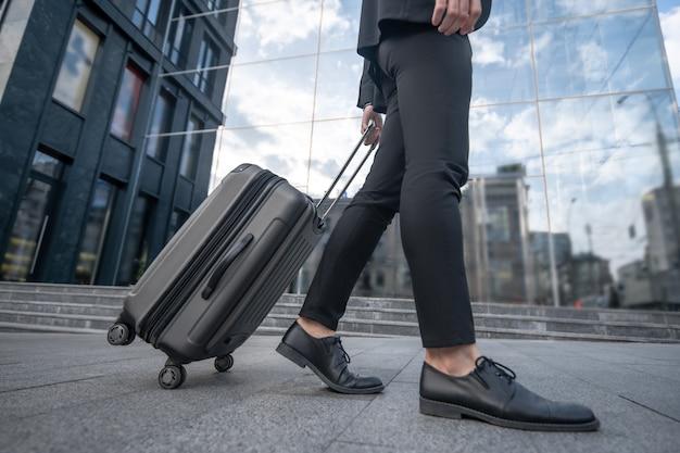Крупным планом изображение мужчины в черном костюме с чемоданом