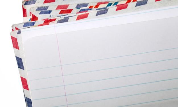Закройте изображение чистого листа бумаги и конвертов за ним.