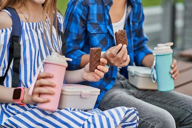 분홍색 도시락과 파란색 보온병, 케이크가 있는 어린이 점심 사진을 클로즈업하세요.