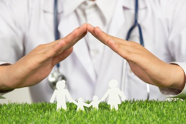 가족 구성원 모델 위에 집의 기호를 게시하는 의사의 손 사진을 닫습니다