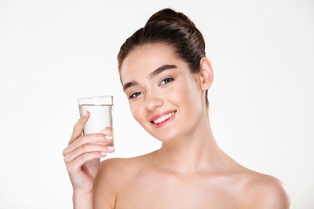 Крупным планом картина радостной великолепной женщины, полуголой пьющей минеральную воду из прозрачного стекла с улыбкой