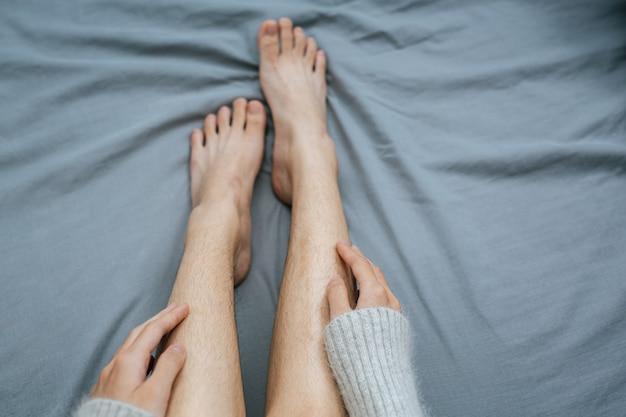 ベッドの上でそっと足に触れている手の写真をクローズアップ