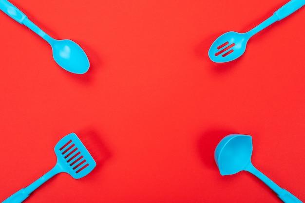 Крупным планом картина кухонной утвари с copyspace на красном