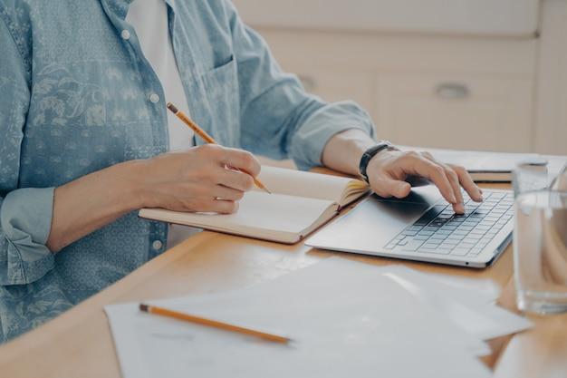 ウェブサイトで新しい記事を書いたり、キッチンの木製テーブルで議題にメモを書いたりするためにラップトップで入力している男性の手の写真をクローズアップします。フリーランスと在宅勤務の概念
