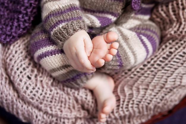새로 태어난 아기 발과 손의 사진을 닫습니다