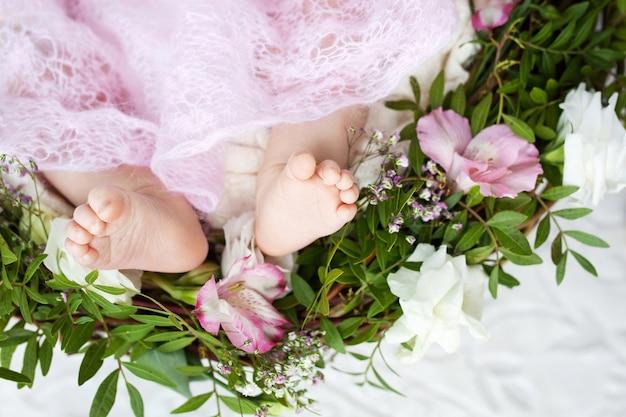 ニットの格子縞と花に生まれたばかりの赤ちゃんの足の写真を閉じる