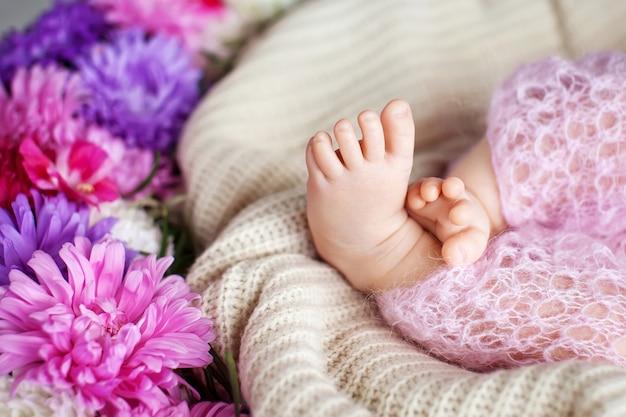 니트 격자 무늬에 새로 태어난 아기 발의 사진을 닫습니다