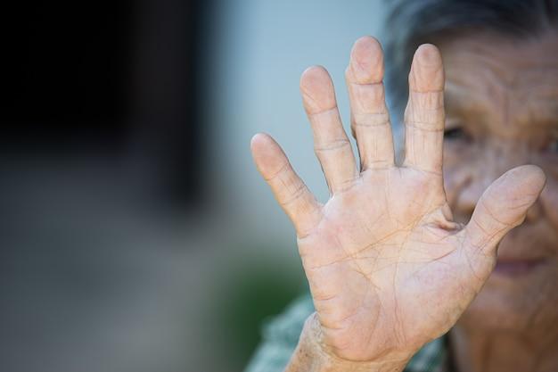 안티 기호를 보여주는 늙은 여자의 손 그림을 닫습니다