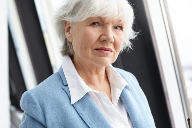 짧은 회색 머리, 주름 및 세련된 정장 옷을 입고 일광에 창 옆에 서 자연 메이크업으로 은퇴에 심각한 아름다운 노인 유럽 여성의 사진을 닫습니다