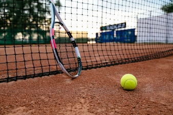 Close-up picture of tennis racket and ball on the clay court. View through the net.