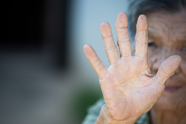 Close up picture of old woman's hand showing anti symbol